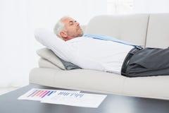 Бизнесмен спать на софе с диаграммами на таблице в живущей комнате Стоковое фото RF