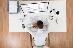 Бизнесмен спать перед компьютером на столе Стоковые Фото