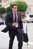 Бизнесмен спеша вдоль улицы держа на вынос кофе стоковое изображение