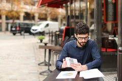 Бизнесмен споря smartphone и читая газеты на плате кафа Стоковые Фотографии RF