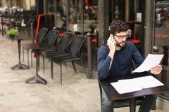 Бизнесмен споря smartphone и читая газеты на плате кафа Стоковые Фото