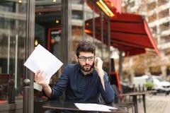 Бизнесмен споря smartphone и читая газеты на плате кафа Стоковое Фото