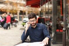Бизнесмен споря smartphone и читая газеты на плате кафа Стоковая Фотография RF