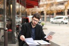 Бизнесмен споря smartphone и читая газеты на плате кафа Стоковая Фотография