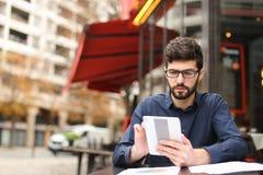 Бизнесмен споря smartphone и читая газеты на плате кафа Стоковые Изображения RF