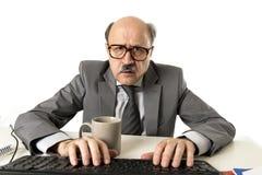 Бизнесмен старшия зрелый занятый с лысой головой на его деятельности 60s усиленной и расстроенной на столе компьтер-книжки компью Стоковые Фотографии RF