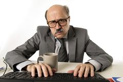 Бизнесмен старшия зрелый занятый с лысой головой на его деятельности 60s усиленной и расстроенной на столе компьтер-книжки компью Стоковые Изображения