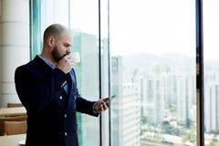 Бизнесмен стоит в окне современного офиса внутреннем близко с видом на город Стоковое Изображение RF