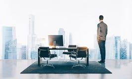 Бизнесмен стоит в современном офисе и смотреть город горизонтально стоковое изображение