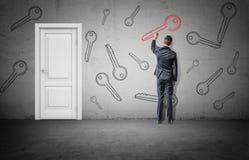 Бизнесмен стоит около белой закрытой двери и рисует большой красный ключ на стене около много черных ключей Стоковое фото RF