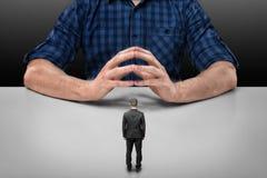 Бизнесмен стоит перед большим человеком сидя при его сжиманные пальцы Стоковые Изображения