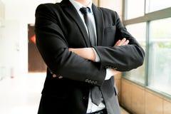 Бизнесмен стоит с его предпосылкой пересеченной рукой запачканной Стоковая Фотография RF