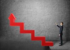 Бизнесмен стоя близко лестницы в форме красной стрелки указывая вверх Стоковые Изображения