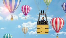 Бизнесмен стоя внутри корзины воздушного шара, пока он плавает в небо среди много других воздушных шаров Стоковая Фотография RF