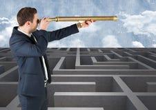 Бизнесмен стоя в лабиринте и смотря от телескопа Стоковые Изображения