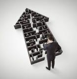 Бизнесмен стоя в лабиринте формы стрелки Стоковое Фото