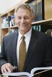 Бизнесмен стоя в библиотеке с книгой Стоковые Фотографии RF