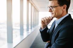 Бизнесмен стоя в офисе и думать Стоковое Изображение