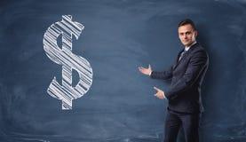 Бизнесмен стоя и показывая знак доллара нарисованный на классн классном Стоковая Фотография
