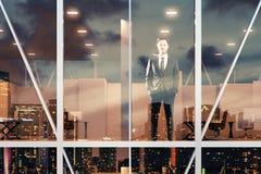 Бизнесмен стоя и смотря вне окно офиса на стоковые изображения