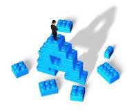 Бизнесмен стоя на блоках стога формы письма a алфавита Стоковое Фото