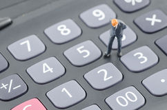 Бизнесмен стоя на калькуляторе Стоковые Фото