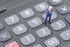 Бизнесмен стоя на калькуляторе Стоковое Изображение