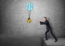 Бизнесмен стоя на крае достигая для мешков денег Стоковые Изображения