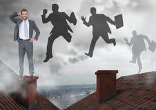 Бизнесмен стоя на крышах и силуэтах бизнесменов скача с печной трубой и пасмурным городом Стоковое Изображение RF