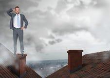 Бизнесмен стоя на крышах с печной трубой и пасмурным городом Стоковое фото RF