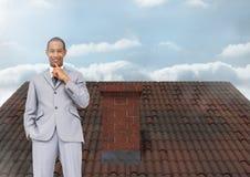 Бизнесмен стоя на крыше с печной трубой и небом Стоковые Фото