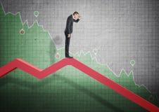 Бизнесмен стоя на падая диаграмме и всматриваясь в будущее Стоковые Фотографии RF