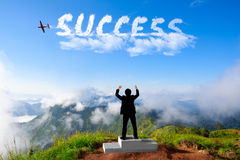 Бизнесмен стоя на подиуме победителя на горах Стоковое Изображение RF
