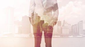 Бизнесмен стоя на предпосылке городского пейзажа Стоковое Изображение RF