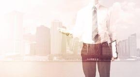Бизнесмен стоя на предпосылке городского пейзажа Стоковое фото RF