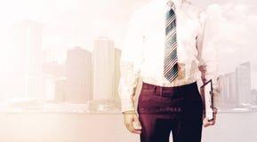 Бизнесмен стоя на предпосылке городского пейзажа Стоковое Изображение