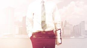 Бизнесмен стоя на предпосылке городского пейзажа Стоковые Фотографии RF