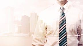 Бизнесмен стоя на предпосылке городского пейзажа Стоковые Изображения