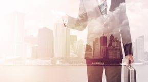 Бизнесмен стоя на предпосылке городского пейзажа Стоковые Фото