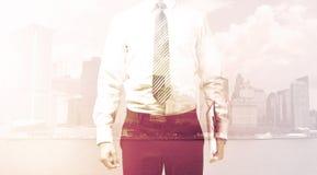 Бизнесмен стоя на предпосылке городского пейзажа Стоковое Фото