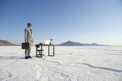 Бизнесмен стоя на столе мобильного офиса Outdoors стоковая фотография rf