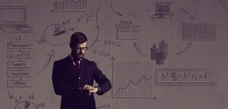 Бизнесмен стоя над схематической предпосылкой Дело и  Стоковое Изображение