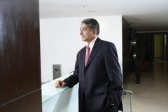 Бизнесмен стоя на счетчике регистрации Стоковые Фотографии RF