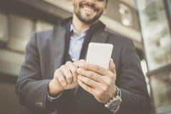 Бизнесмен стоя на улице города и держа умный phon стоковое изображение rf