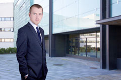 Бизнесмен стоя на улице против офисного здания Стоковые Фото
