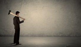 Бизнесмен стоя перед grungy стеной с молотком Стоковое Изображение RF