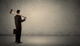 Бизнесмен стоя перед grungy стеной с молотком Стоковое Изображение
