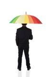 Бизнесмен стоя позади с multicolor зонтиком стоковые изображения