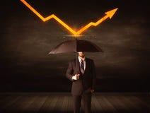 Бизнесмен стоя при зонтик держа оранжевую стрелку стоковая фотография