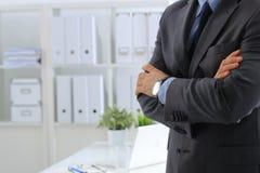 Бизнесмен стоя при оружия пересеченные в офис Стоковые Фотографии RF